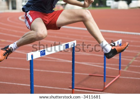 man is jumping over the hurdle - stock photo