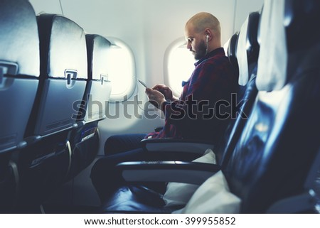Man is listening to music in headphones and chatting in social network via mobile phone, during his flying in an airplane. Hipster guy is watching video on cell telephone , while is sitting in plane - stock photo