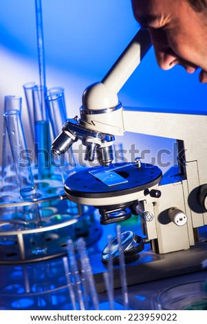 Man is looking into the ocular of microscope, doing reseach - stock photo