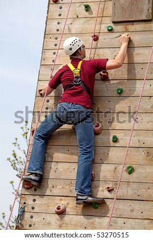 man is on climbing wall in the nature - stock photo