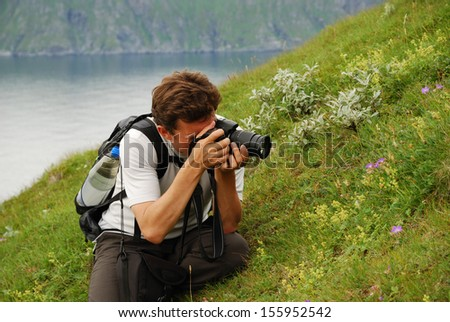 Man is photographing flowers in green grass. He is sitting in the blooming slope of summer Soroya. There are a blue fjord and green mountains in the background.