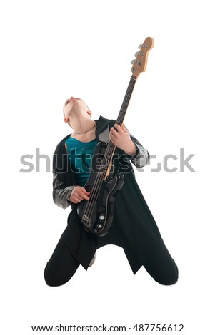Man is playing the electric guitar in dark clothes , standing on his knees and looking up