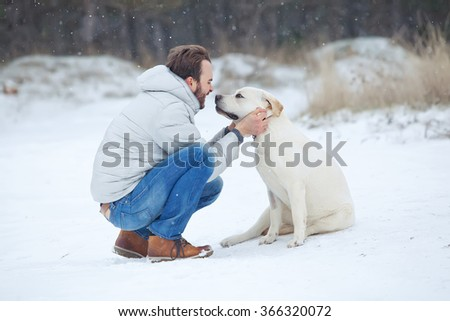 Man is playing with his yellow labrador retriever in winter landscape