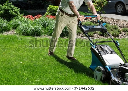 Man is pushing lawn mower to mown grass