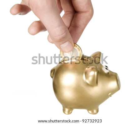 Man is putting coin to golden piggybank, savings concept