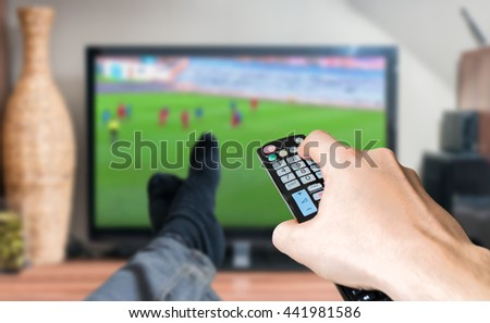 Man is relaxing with legs on table and is watching football match on tv and holds remote controller. - stock photo