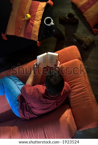 Man is resting and reading a book on the couch at home. - stock photo