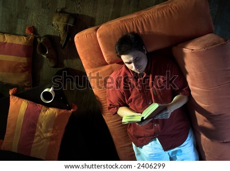 Man is resting on the couch and reading a book at home. - stock photo