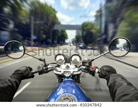 Man is riding a motorcycle on big speed by the asphalt road