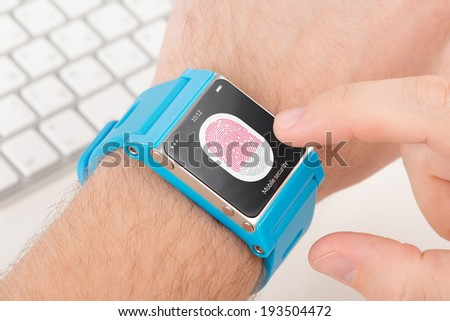 Man is scanning fingerprint for mobile security with blue smart watch. - stock photo
