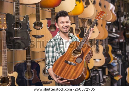 Man is showing guitar in music store.
