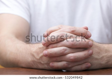 Man is sitting and holding his hands together on a wooden table. Like praying or sitting in a meeting and listening.