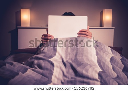 Man is sitting in bed behind his laptop - stock photo