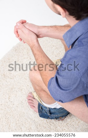 Man is sitting on the toilet. View from above. - stock photo