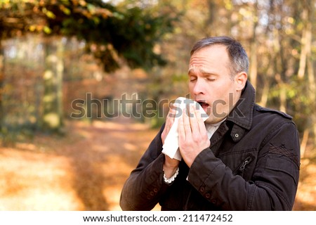 Man is sneezing - stock photo