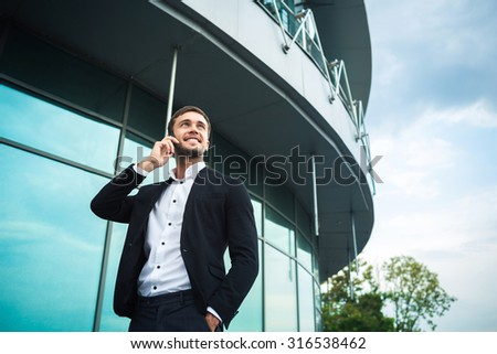 Man is standing and looking to the sky. He wears a smart dress code with white shirt. He is talking on the phone