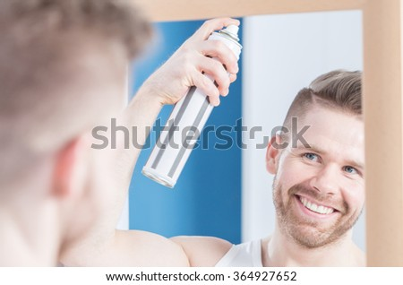 Man is styling his hair using hairspray - stock photo