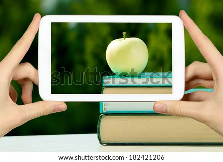 Man is taking photo of apple on the book with white tablet - stock photo