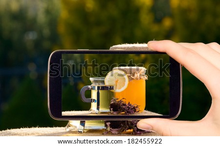 Man is taking photo of jar with honey with smart mobile phone - stock photo