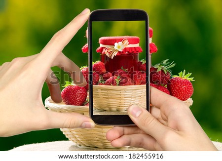 Man is taking photo of strawberries with smart mobile phone - stock photo