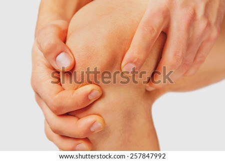 Man is touching his knee joint due to acute pain on a white background - stock photo