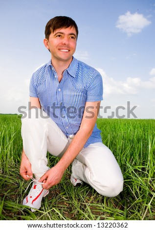 Man is Tying Laces In A Green Field - stock photo