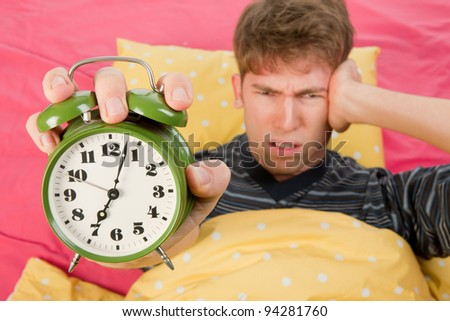 man is waking up with alarm clock with bells - stock photo