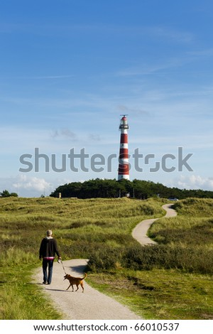 Man is walking his dog near the lighthouse - stock photo
