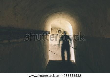 Man is walking through dark underground - stock photo
