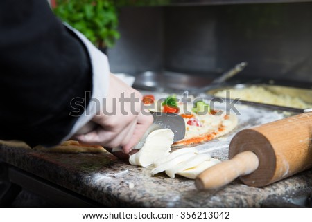 Man is working at the kitchen. He cut some ingredients for pizza and he uses very sharp knife. He's going to use mozzarella cheese as a top of pizza - stock photo