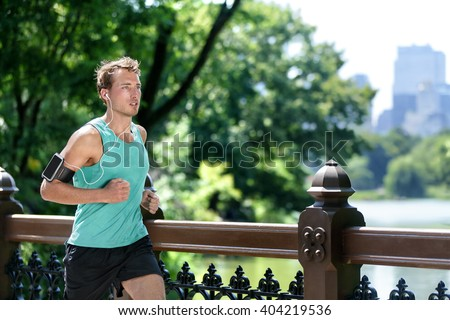 Man jogging in urban city NYC with smartphone armband. Male athlete runner running listening to music playlist on mobile phone app and earphones for workout run in New York's Central Park in summer. - stock photo