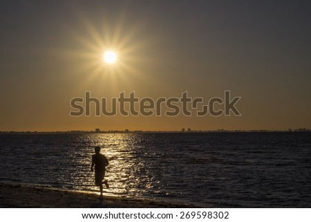 Man Jogging on the Beach During Sunrise - stock photo