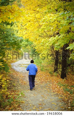 Man jogging towards end of woodland trail in Fall - stock photo