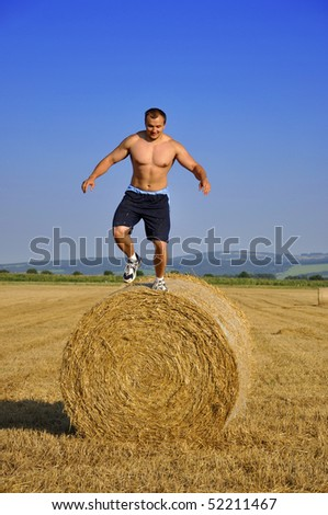 Man jump down from bale straw - stock photo