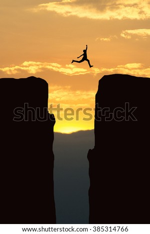Man jump through the gap between hill.man jumping over cliff on sunset background ,Business concept idea