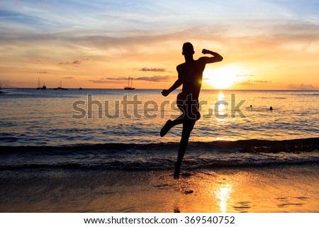 Man jumping  at Sunset on beach in Santiago island in Cape Verde - Cabo Verde - stock photo