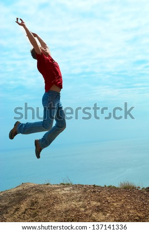 Man jumping cliff against sea and mountain with blue sky - stock photo