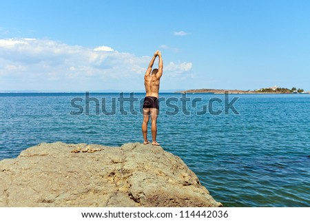 man jumping from a rock into the sea