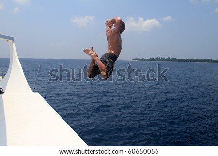 Man jumping from boat into the sea - stock photo