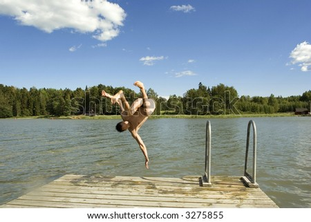 Man jumping from the pier to the sea - stock photo