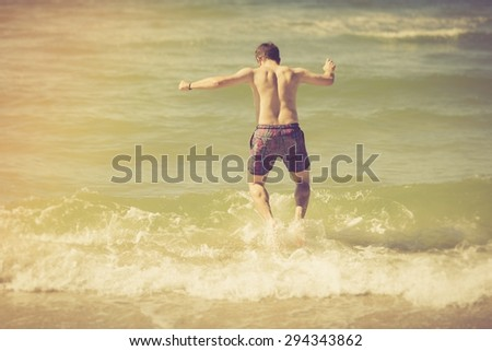 Man jumping in sea water. Summertime photo with sea shore and man jumping in water - stock photo