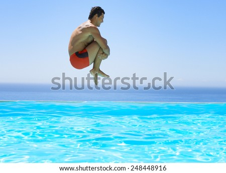 Man jumping in swimming pool - stock photo
