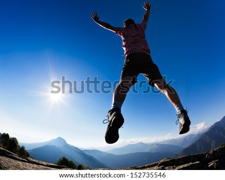 Man jumping in the sunshine against blue sky. Concept: freedom, success, energy, vitality. - stock photo