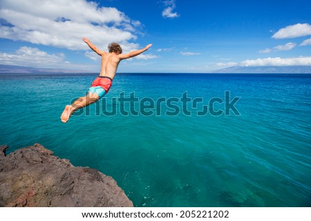 Man jumping off cliff into the ocean. Summer fun lifestyle. - stock photo