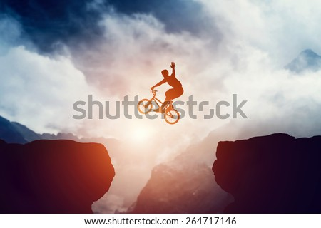 Man jumping on bmx bike over precipice in mountains at sunset. Raising hand showing hello gesture. Extreme sport, risk, cycling. - stock photo
