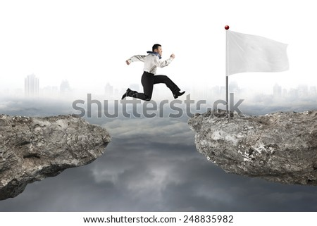 Man jumping on cliff with blank white flag and gray cloudy cityscape background - stock photo