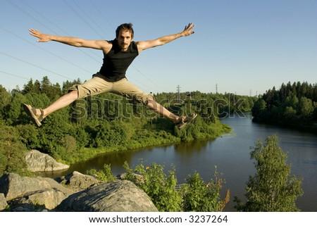 Man jumping on rocks - stock photo