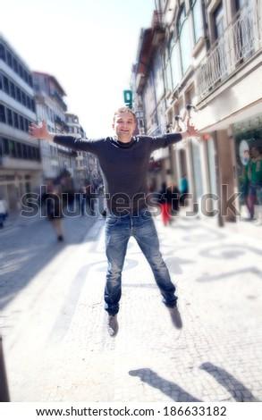 Man jumping on street, happy. - stock photo