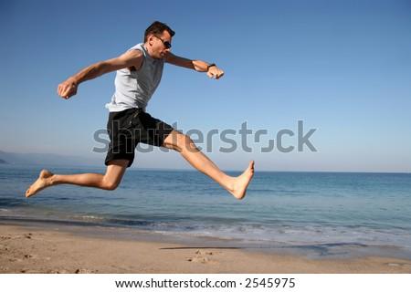 Man jumping on the beach - stock photo