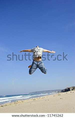 Man jumping on the beach and having fun - stock photo